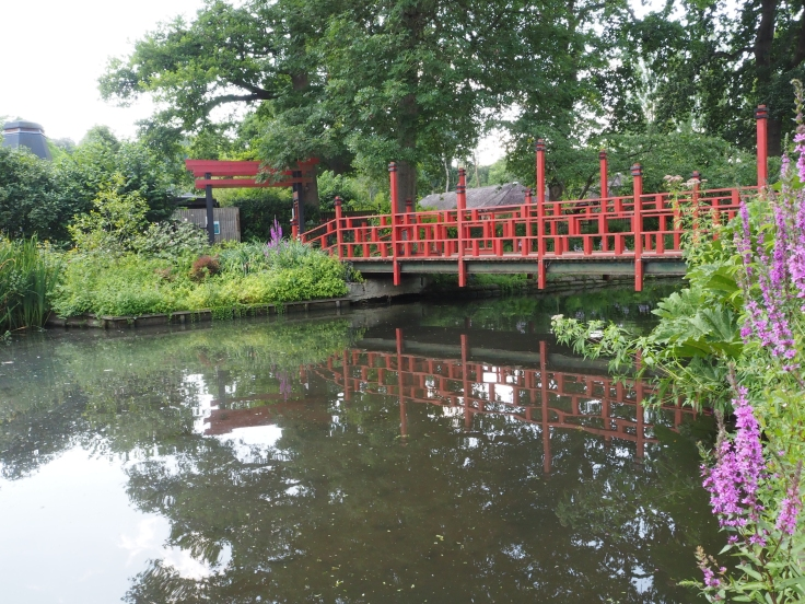 An Oriental style bridge goes over a small lake